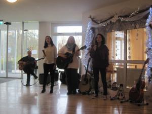 Drei Frauen stehen auf einer Bühne und singen.