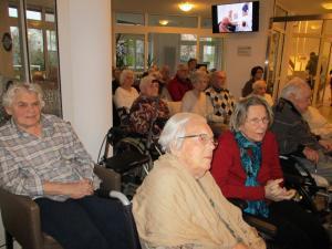 Alte Menschen sitzen zusammen auf Stühlen.