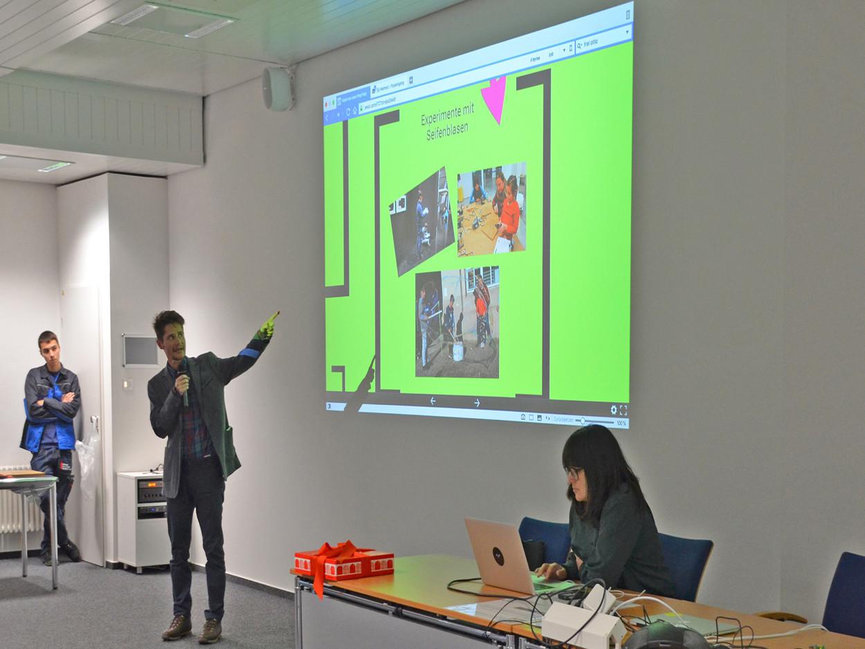 Ein Mann hält einen Vortrag und zeigt eine Präsentation.