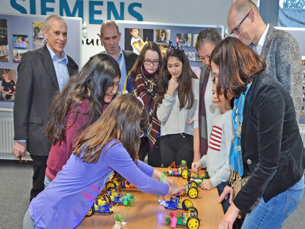 Kinder stehen an einem Tisch und zeigen Erwachsenen ihre Roboter.