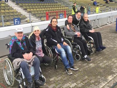 Menschen mit und ohne Rollstuhl sitzen vor einer Tribüne.