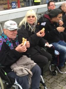 Menschen sitzen zusammen und essen Bratwurst.