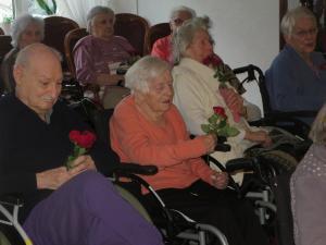 Senior*innen sitzen in Rollstühlen und halten Rosen in den Händen.