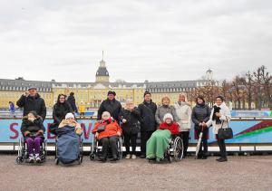 Eine Gruppe von Senioren steht vor dem Karlsruher Schloss.