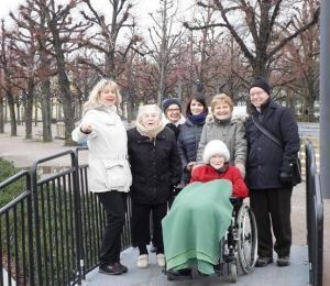 Eine Gruppe von Senioren steht vor dem Karlsruher Schloss im Park.