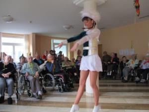 Ein Funkenmariechen steht vor Senioren, die im Rollstuhl sitzen.