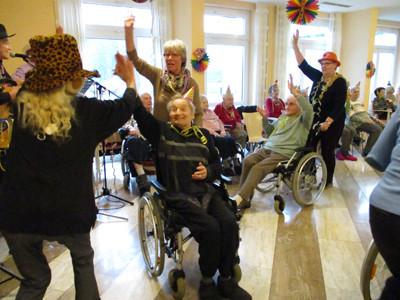 Ein Mann im Rollstuhl tanzt mit anderen Menschen zusammen.