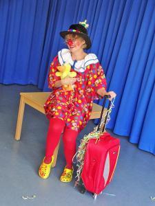 Eine Clownin sitzt auf einem Tisch.