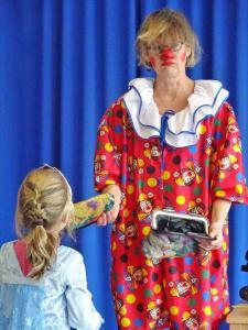 Eine Clownin gibt einem kleinen Mädchen die Hand.