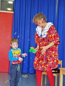 Ein kleiner Junge und eine Clownin lachen zusammen.