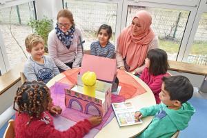 Kinder sitzen mit zwei erwachsenen Frauen an einem Tisch und unterhalten sich.