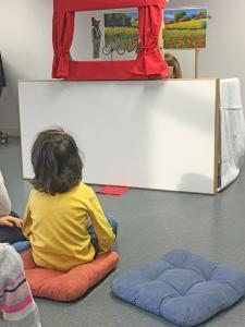 Ein Kind sitzt vor einem Puppentheater.