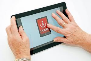 Eine Seniorin streicht über ein Tablet mit einem I-CARE Logo.