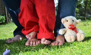 Zwei Erwachsenenfüße und ein paar Kinderfüßen stehen auf der Wiese.