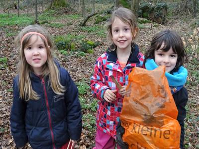 Drei Kita Kinder stehen im Wald und lächeln.