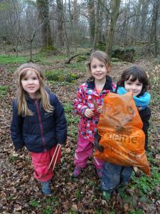 Kindergartenkinder stehen im Wald und lächeln.