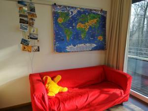 Eine rote Couch steht vor einer Wand an der eine Weltkarte hängt.