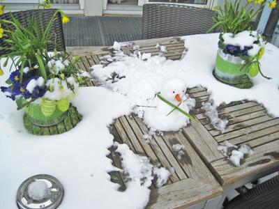 Schnee auf einem Holztisch mit Osterdekoration.
