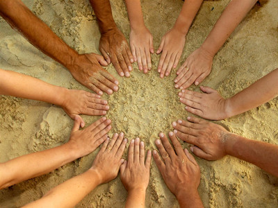 Hände mit verschiedenen Hauttönen bilden einen Kreis im Sand.