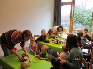 Kita Kinder und Erwachsene spielen mit Hasen.