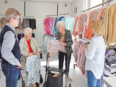 Zwei Seniorinnen stehen vor Kleiderständern und schauen sich Bekleidung an.
