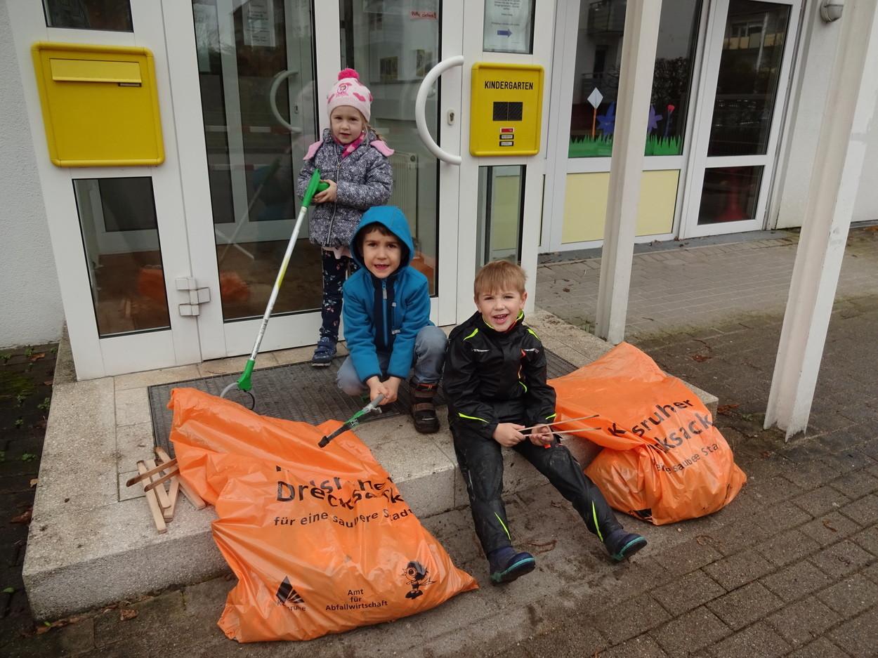 Kinder sammeln Müll auf der Straße.