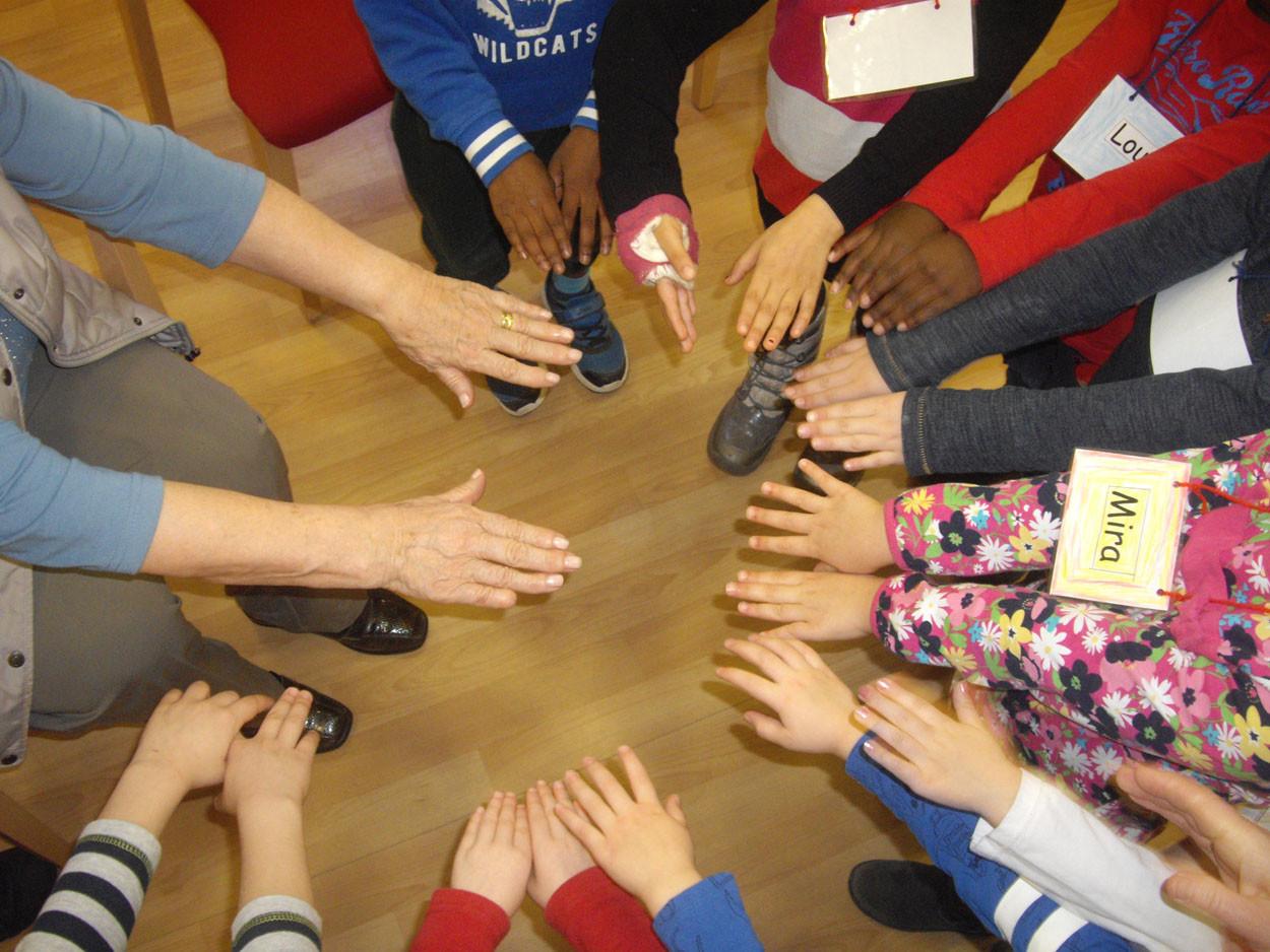 Hände von alten und jungen Menschen strecken sich in einem Kreis.