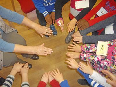 Alte und junge Hände mit verschiedenen Hautfarben berühren sich in einem Kreis.
