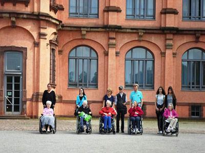 Senioren in Rollstühlen sitzen vor dem Schloss Gottesaue mit ihren Betreuern.