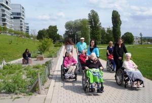 Senioren sitzen in ihren Rollstühlen und spazieren mit Betreuern durch den Otto-Dullenkopfpark.