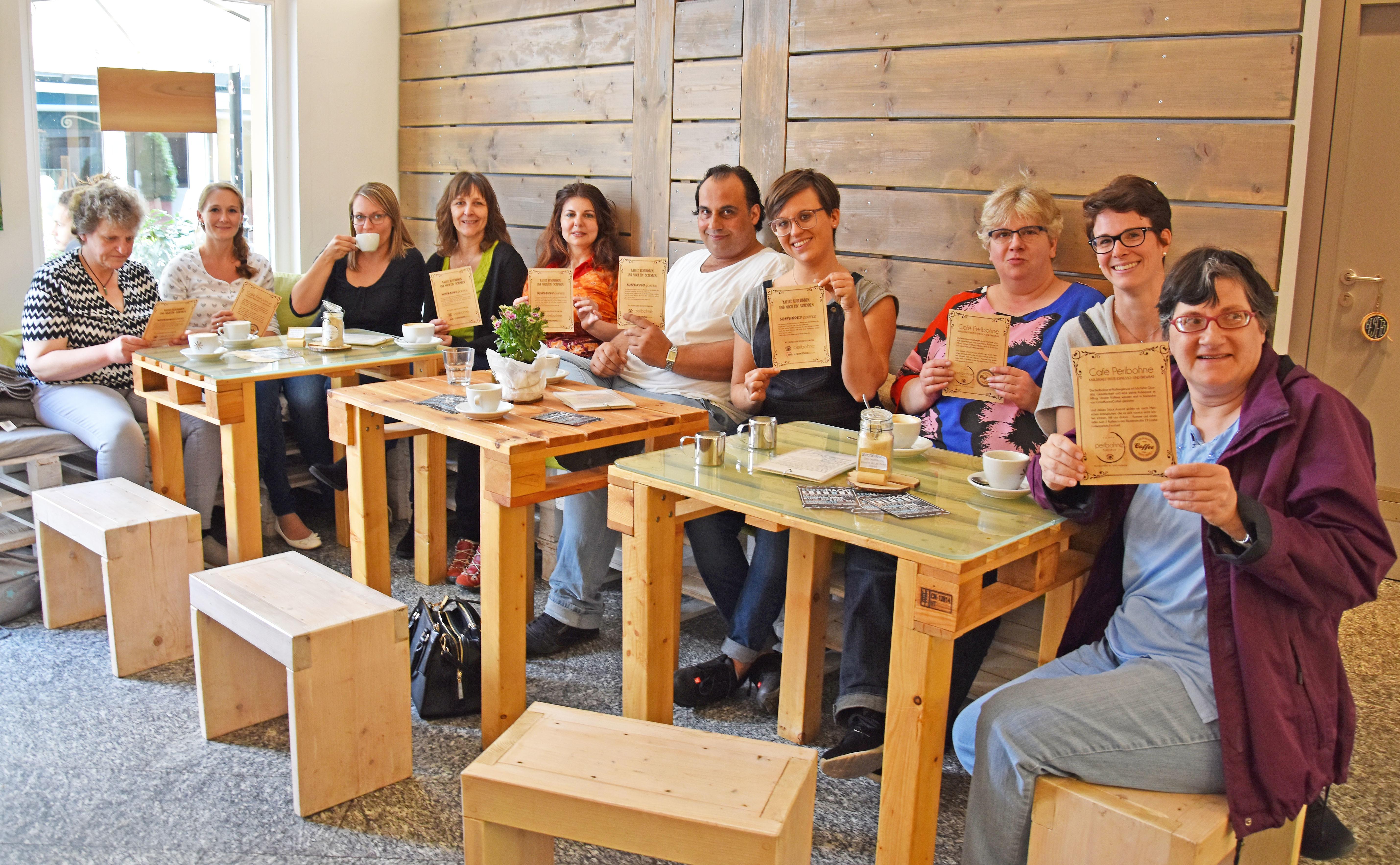Menschen sitzen an einem Tisch halten Zettel in die Luft und trinken Kaffee.