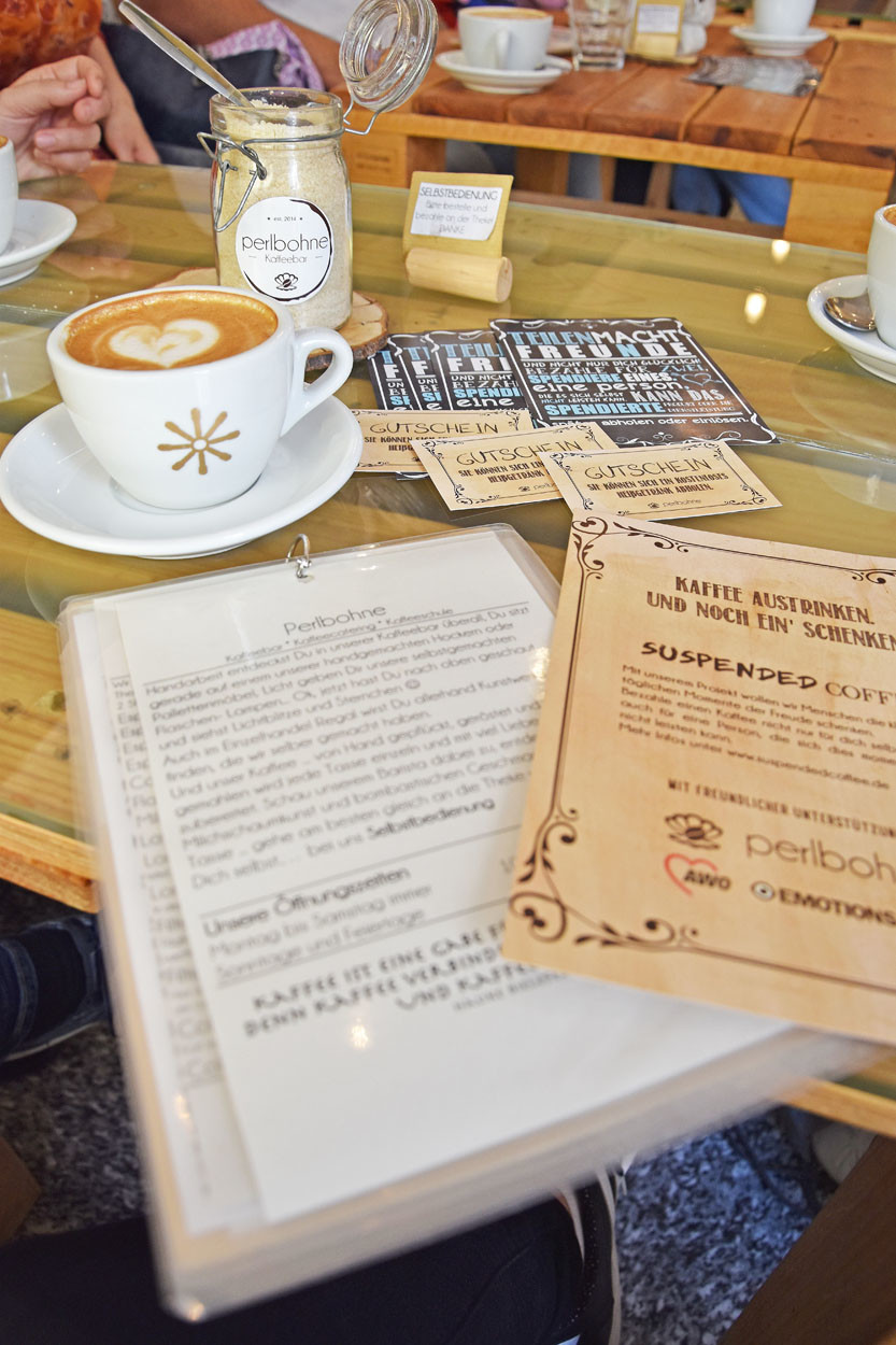 Auf einem Tisch steht eine Kaffeetasse danben liegen Gutscheine und Flyer.