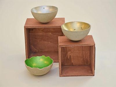 Zwei Betonschalen liegen auf Holzkisten und sind silber und gold angemalt. Daneben liegt eine Schale in grün.
