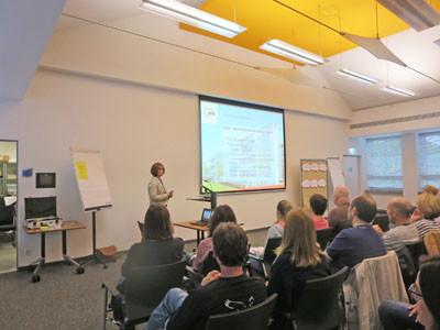 Eine Frau hält einen Vortrag mit einer Power Point Präsentation.