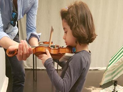 Ein kleins Mädchen hält eine Geige fest, ein Erwachsener hilft ihr dabei.