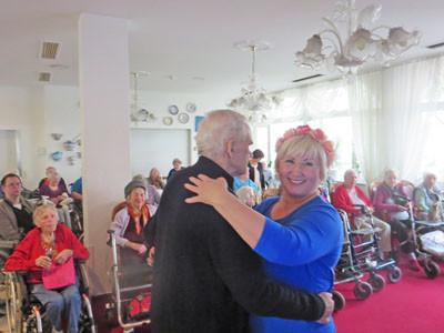 Ein Senior und eine Frau tanzen zusammen im Seniorenheim.