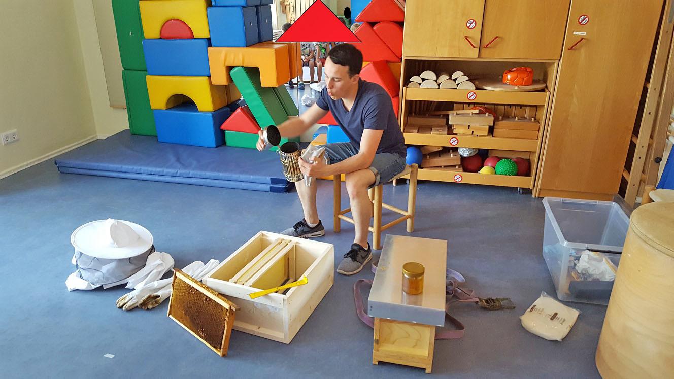 Ein Mann sitzt auf dem Boden und zeigt seine Imkerausrüstung.