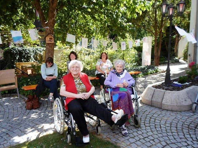 Menschen sitzen in Rollstühlen in einem Hof.