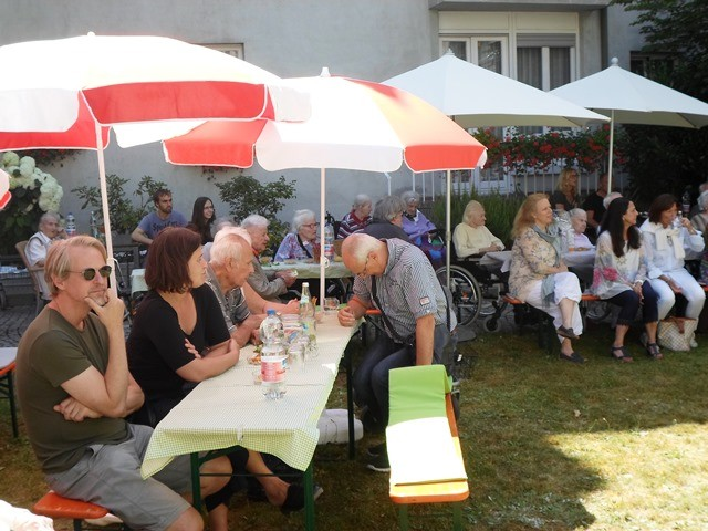 Menschen sitzen auf Bierbänken an einem Tisch unter Sonnenschirmen.