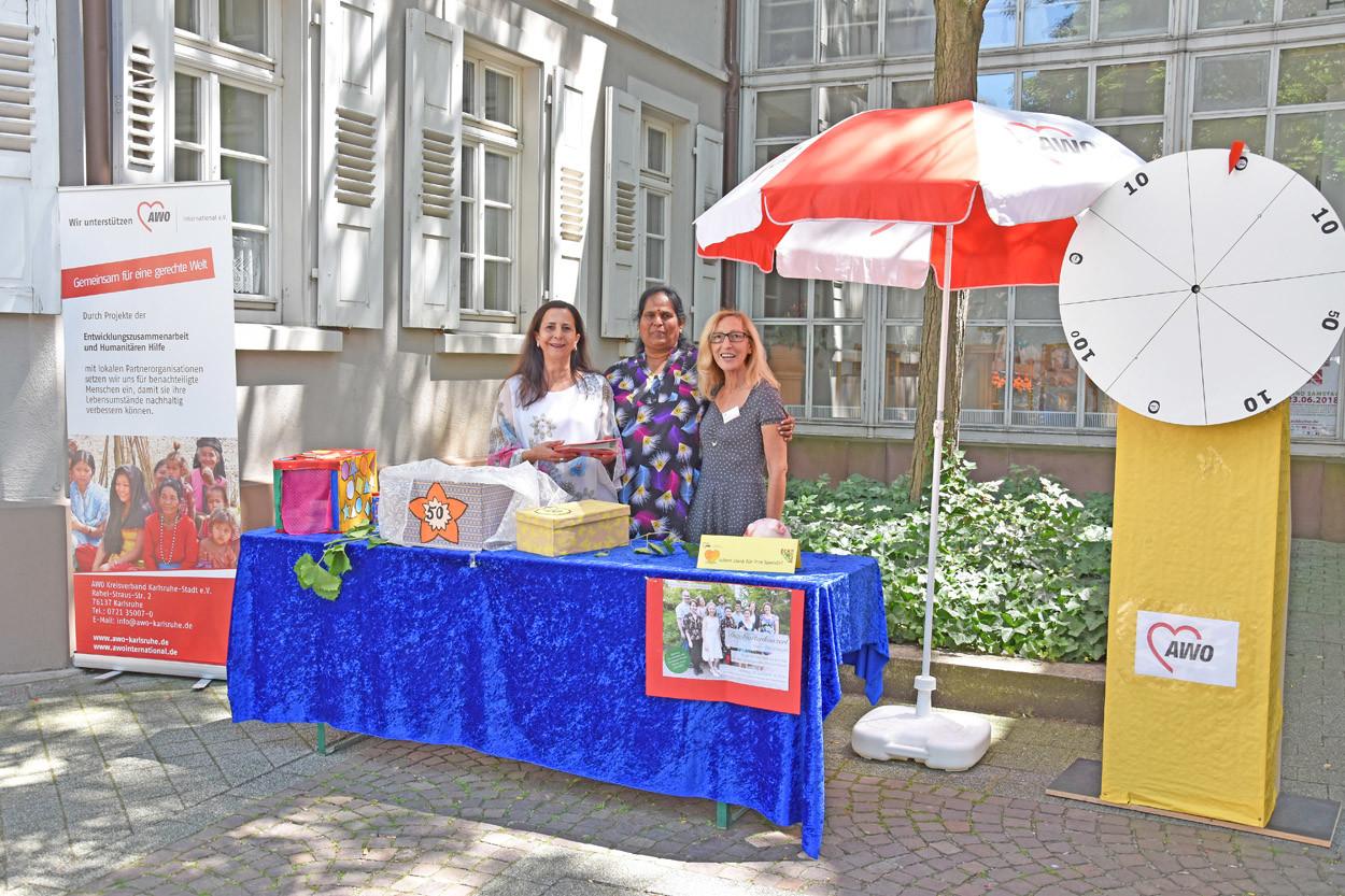 Drei Frauen stehen hinter einem Tisch an einem Infostand.