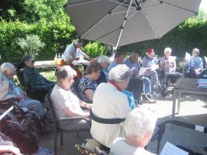Senioren sitzen im Garten unter einem Sonnenschirm.