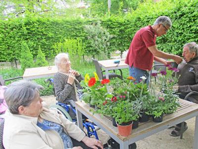 Senioren sitzen im Garten.