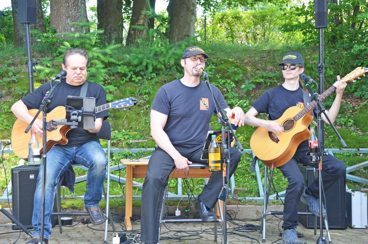 Drei Männer der Gruppe SKY Singers sitzen an ihren Instrumenten und geben ein Konzert.