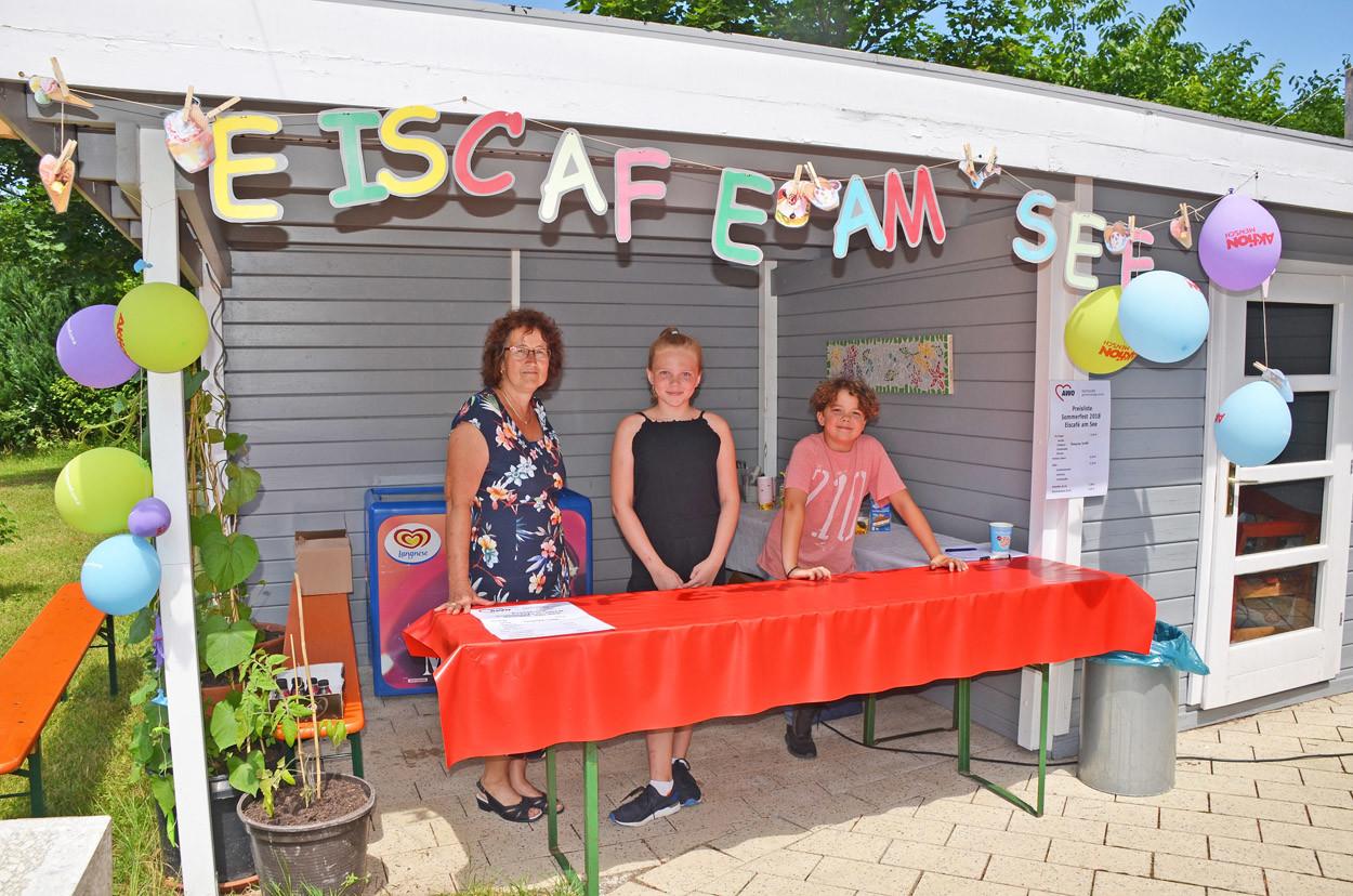 Eine Frau und zwei Kinder stehen an einem Stand und verkaufen Eis.