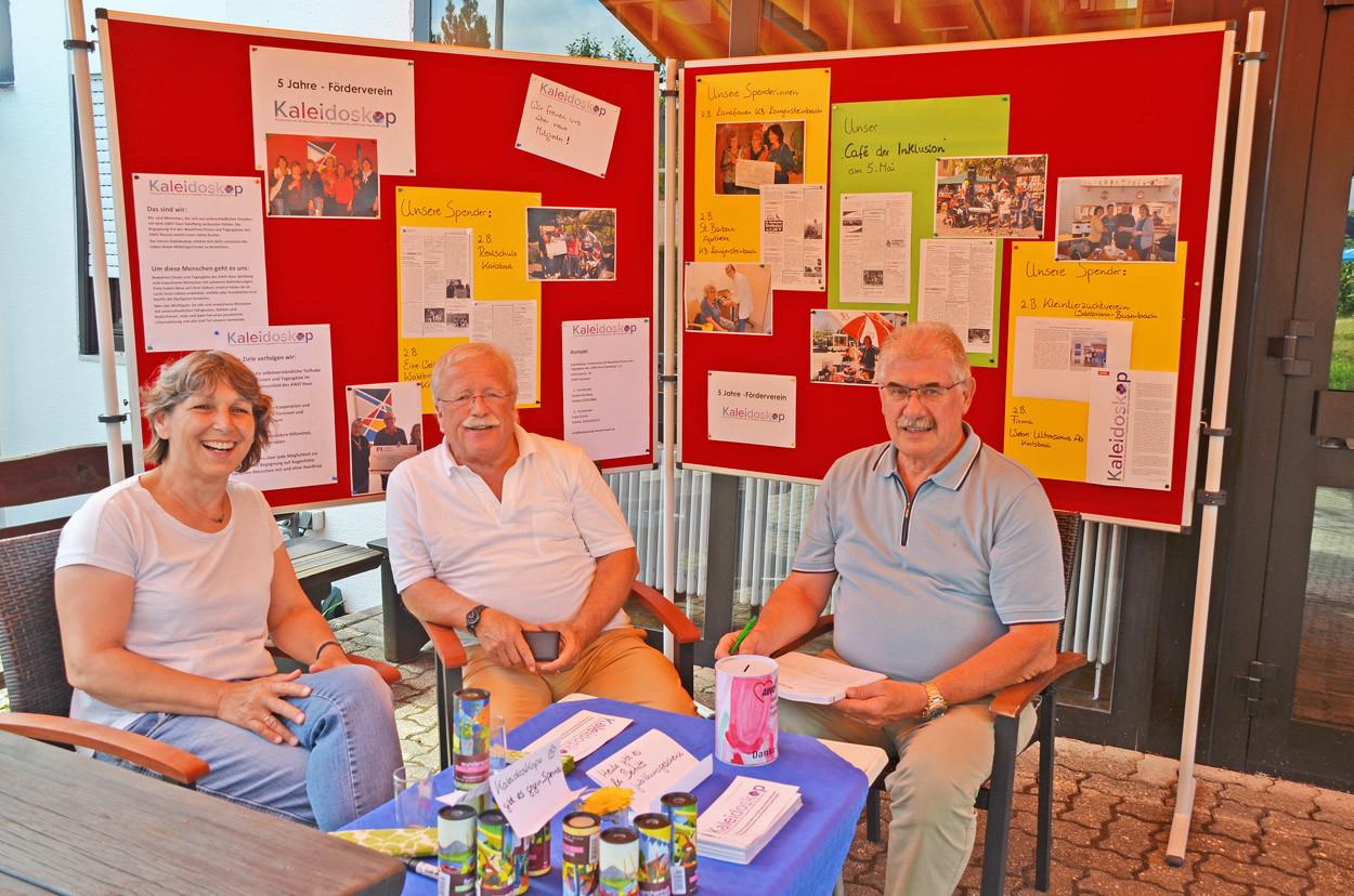 Eine Frau und zwei Männer sitzen vor einer Infowand unter einem Pavillon.