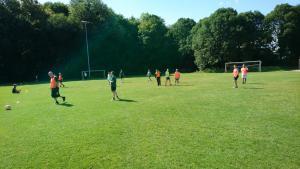 Menschen spielen auf einer Wiese Fußball.