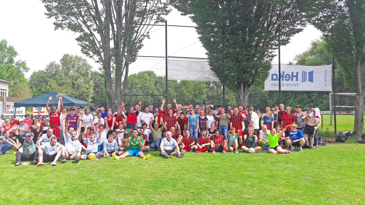 Gruppenfoto von Menschen auf einem Fußballplatz.