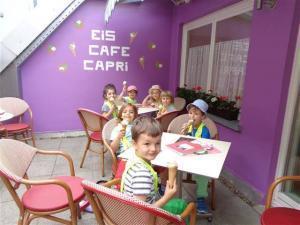 Kinder sitzen an Tischen und essen Eis.