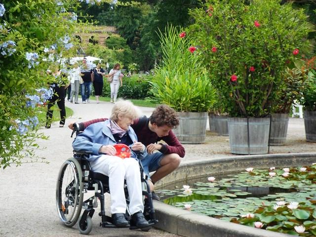 Ein Menschen im ROllstuhl und eine Frau sitzen vor einem Teich im Schlosspark.