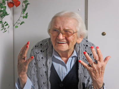 Eine ältere Dame zeigt ihre rot lakierten Nägel.